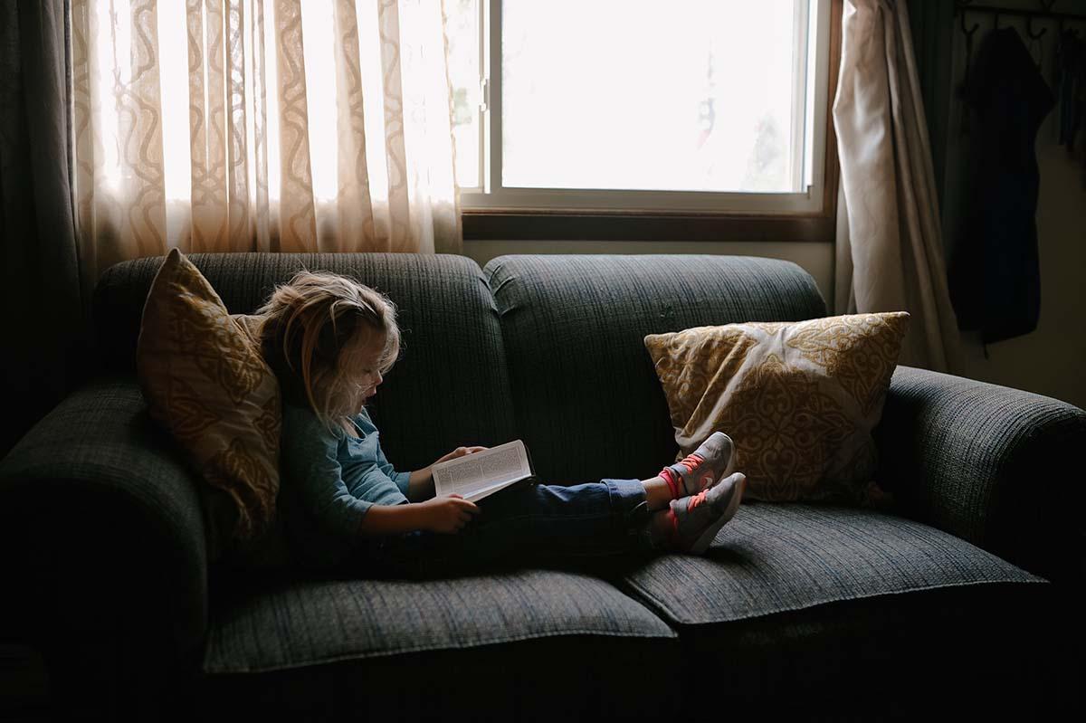 niña leyendo y aprendiendo en su casa